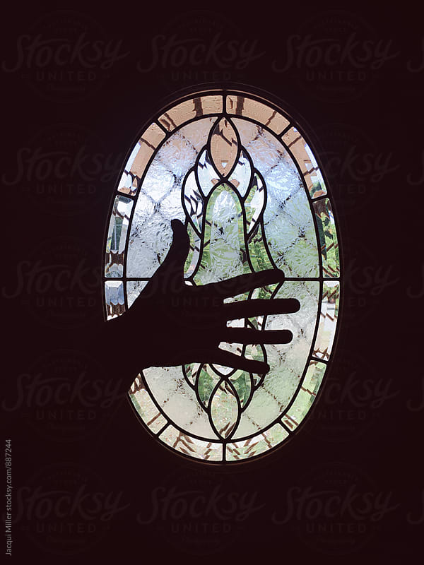 Silhouette of open hand in front of oval window by Jacqui Miller for Stocksy United
