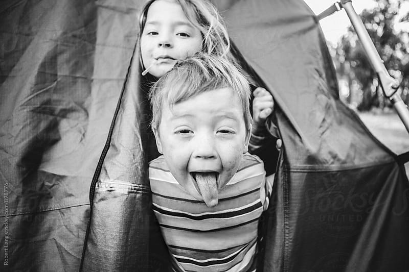 Two children have fun together while camping in a tent by Robert Lang for Stocksy United