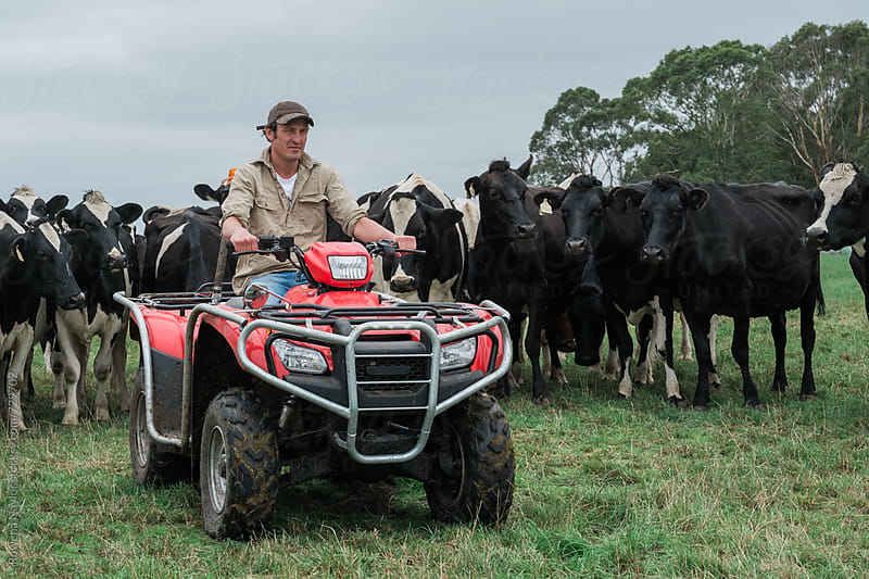 Young Dairy Farmer sitting on ATV by Rowena Naylor for Stocksy United