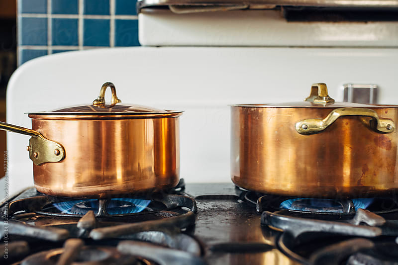 Copper pots on old stove by Gabriel (Gabi) Bucataru for Stocksy United