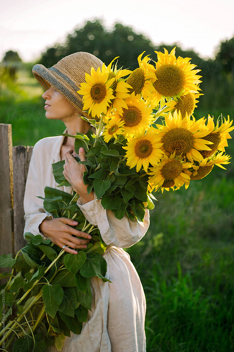 afb6dbd6e1 Girl holding a large bouquet of sunflowers by Duet Postscriptum for Stocksy  United