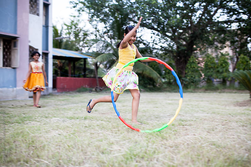Two girls playing and making fun with  hula hoop by PARTHA PAL for Stocksy United