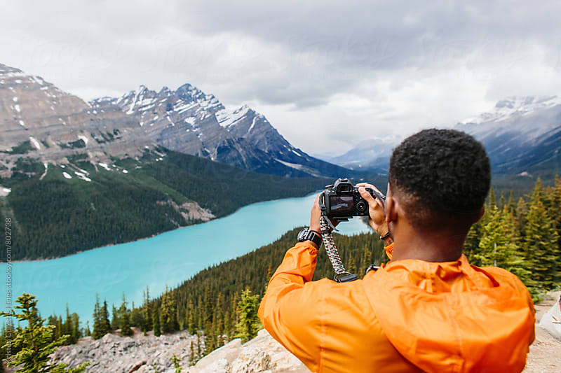 Photographer stands on top of a mountain and taking pictures by Kristen Curette Hines for Stocksy United