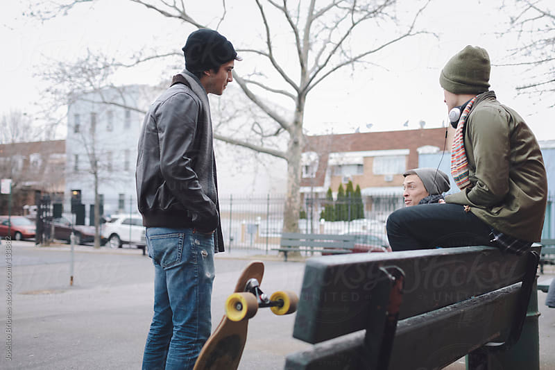 Group of Friends Hanging Out in a Playground with their Skateboard by Joselito Briones for Stocksy United