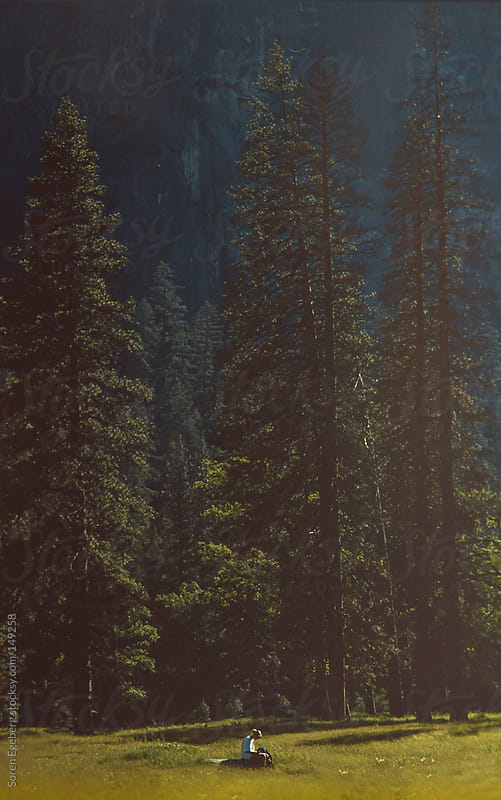 Girl sitting alone in open field with tall pine trees in background by Soren Egeberg for Stocksy United