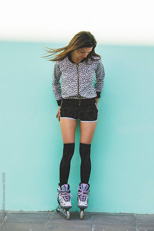 Young roller girl with flying hair standing in front a turquoise wall. by BONNINSTUDIO for Stocksy United