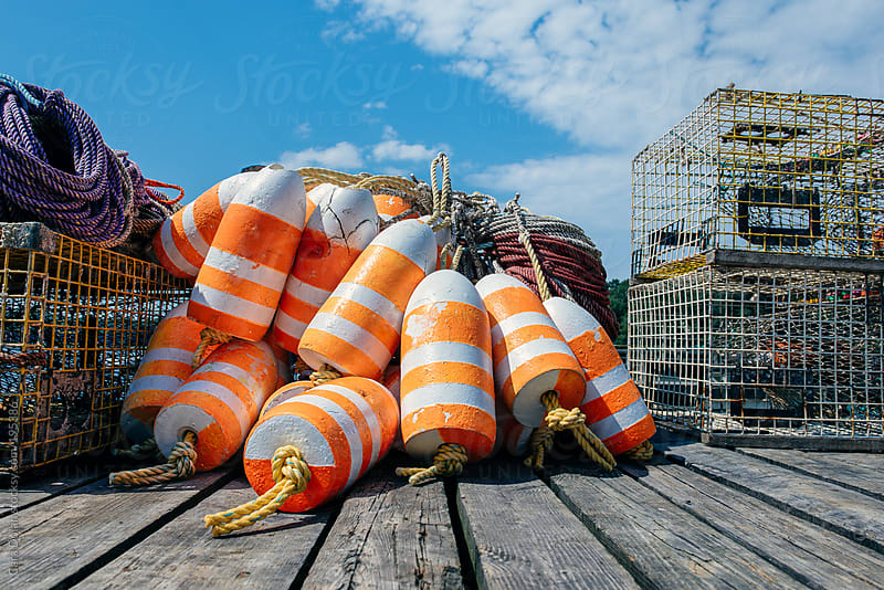 Pile of orange and white lobster trap buoys and traps on a dock by Cara Dolan for Stocksy United