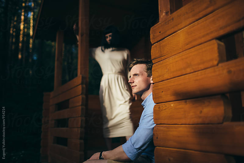 Young couple on the porch of their house in the forest by Evgenij Yulkin for Stocksy United