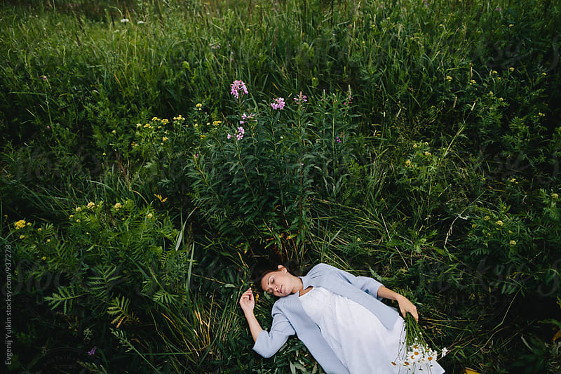 Pregnant female laying in the grass  by Evgenij Yulkin for Stocksy United