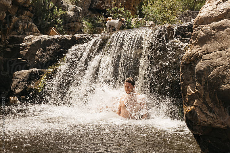 Man enjoying standing under a waterfall in a river by Micky Wiswedel for Stocksy United
