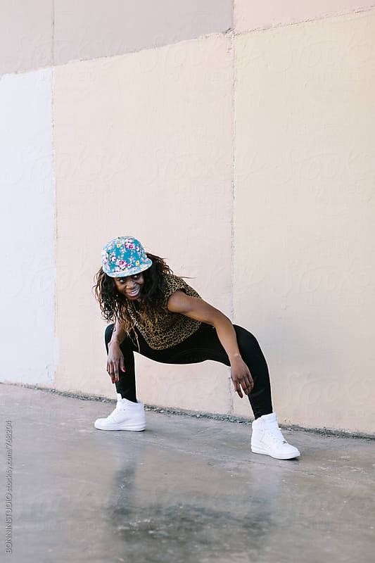 Young african american woman performing street dance in the city. by BONNINSTUDIO for Stocksy United