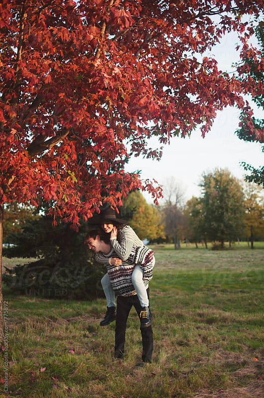 A young couple on a piggy back ride in the fall by Chelsea Victoria for Stocksy United