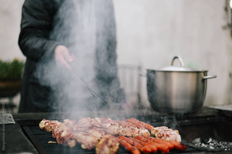 Barbecue and man behind the smoke, just hand  by Marija Kovac for Stocksy United