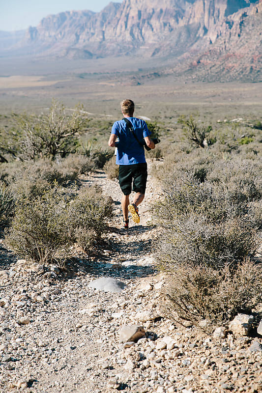 Man running down a dirt trail in the desert by Curtis Kim for Stocksy United