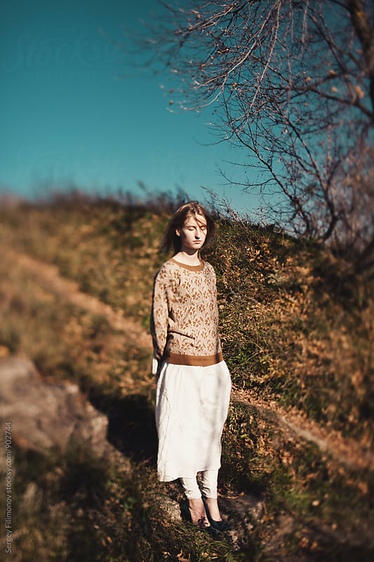 Girl stand on a footpath in the field in the fall by Sergey Filimonov for Stocksy United