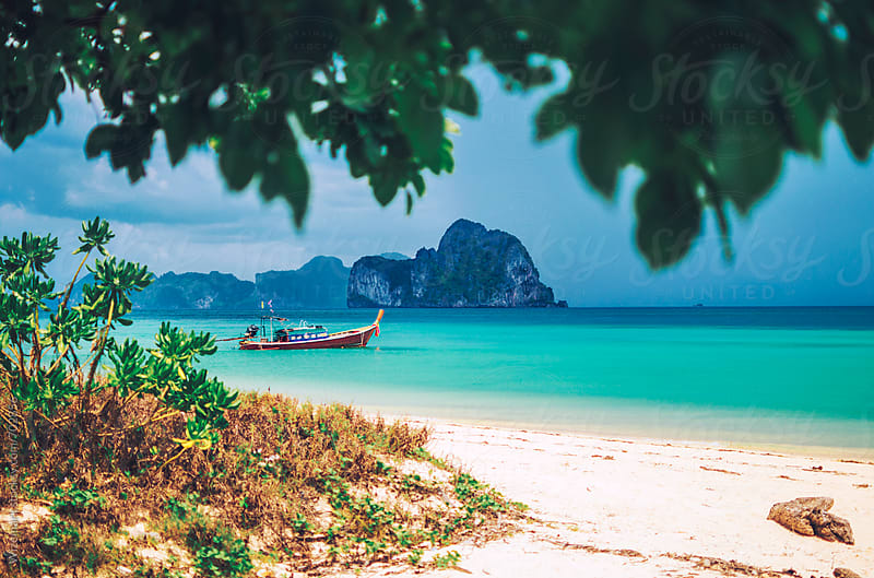 Longtail, wooden Thai fishing boat parked in a beautiful bay by Wizemark for Stocksy United
