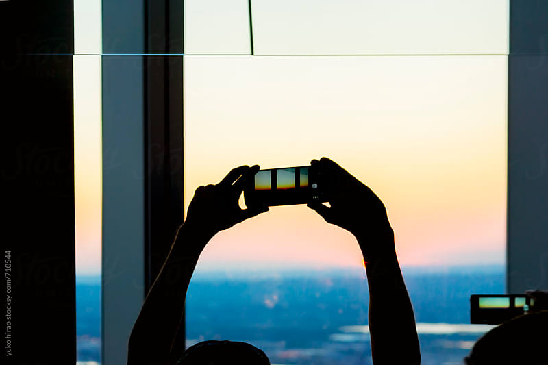 Silhouette of people, taking photos of sunset with mobile phones by yuko hirao for Stocksy United