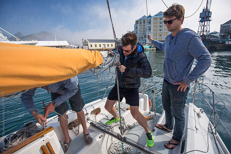 Group of friends rigging ropes and sail of yacht in harbour port preparing for ocean adventure by Jonathan Caramanus for Stocksy United