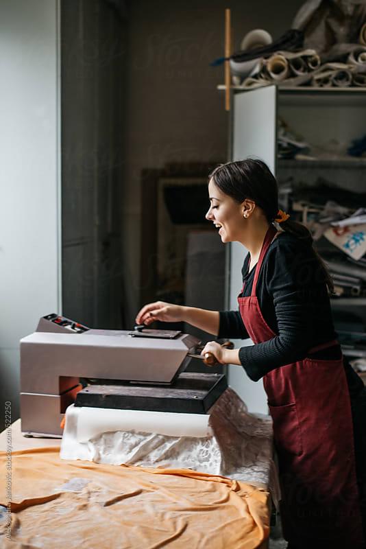 Female textile designer working on the heat transfer press  by Aleksandra Jankovic for Stocksy United