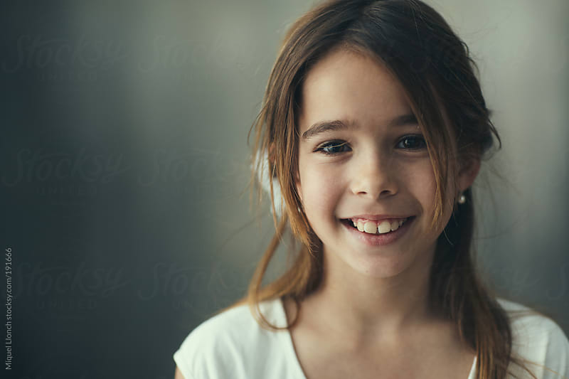Portrait of a smiling little girl by Miquel Llonch for Stocksy United