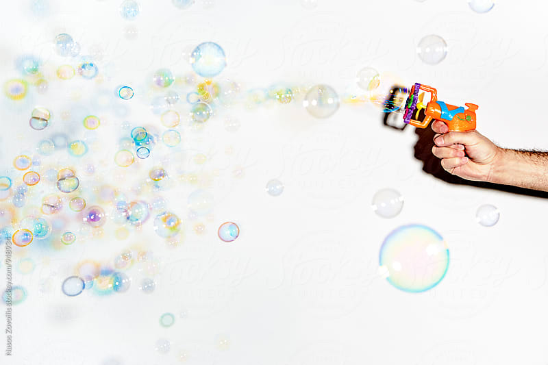 Man holding a pistol which blow soap bubbles by Nasos Zovoilis for Stocksy United