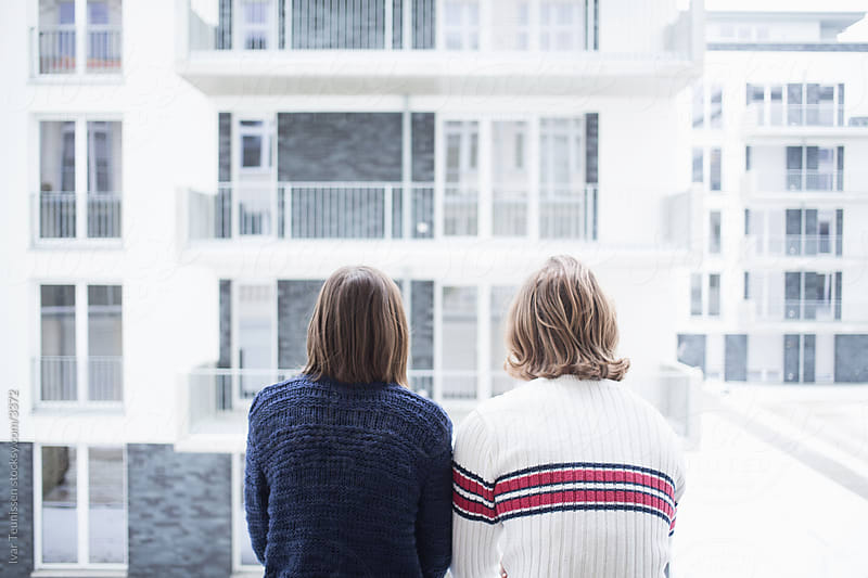 Berlin couple on balcony. by Ivar Teunissen for Stocksy United