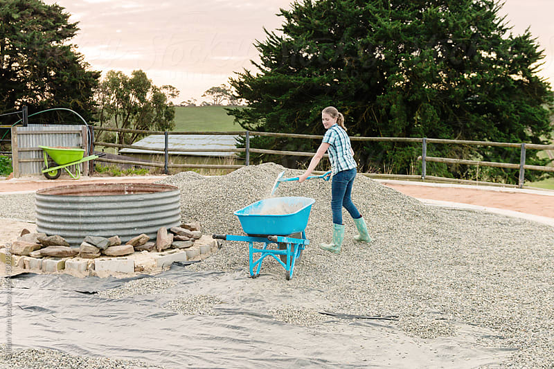 a garden makeover project, teenage girl shovelling stones by Gillian Vann for Stocksy United