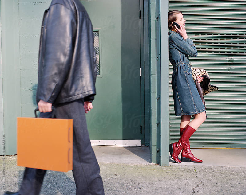Woman talking on cell phone, man holding orange briefcase & walking in foreground by Paul Edmondson for Stocksy United