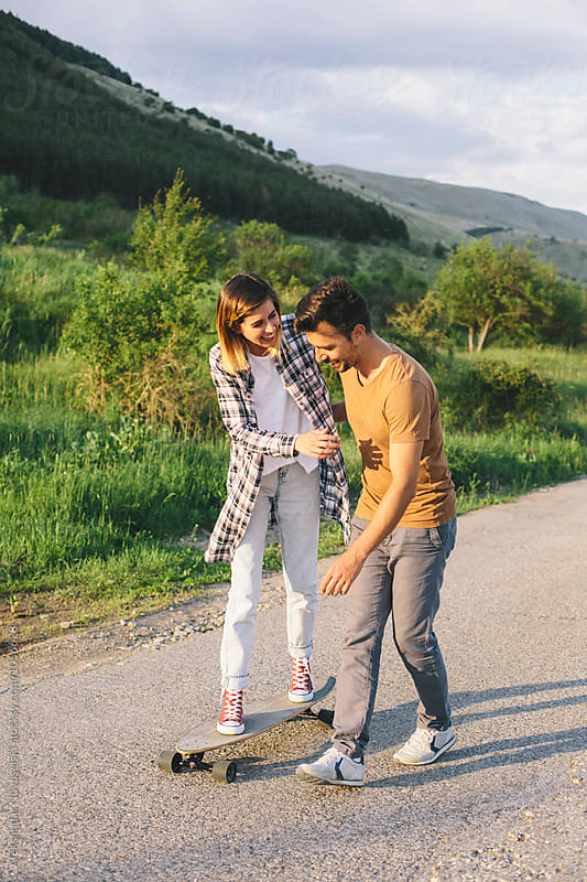 Young couple with longboard by Aleksandar Novoselski for Stocksy United