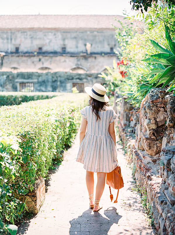 Young woman strolling through garden by Daniel Kim Photography for Stocksy United