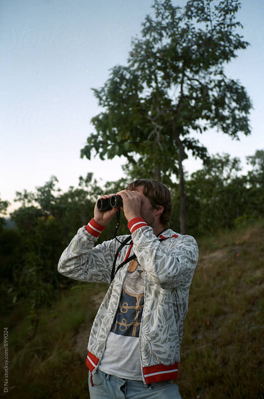 Young man with binoculars by Di Na for Stocksy United