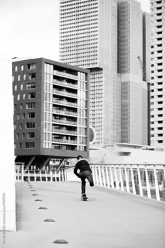 Skater riding on a bridge in the city, surrounded by skyscrapers or buildings. Photo in black and white by Ivo de Bruijn for Stocksy United
