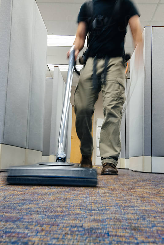 After hours janitor vacuums carpets in an office building by Cara Dolan for Stocksy United