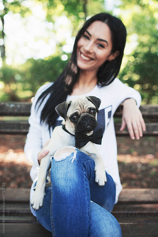 Young woman and her pet pug-dog by Jovana Rikalo for Stocksy United