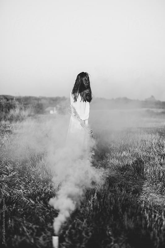 Young woman holding wheat in a smoke cloud by Tatjana Ristanic for Stocksy United