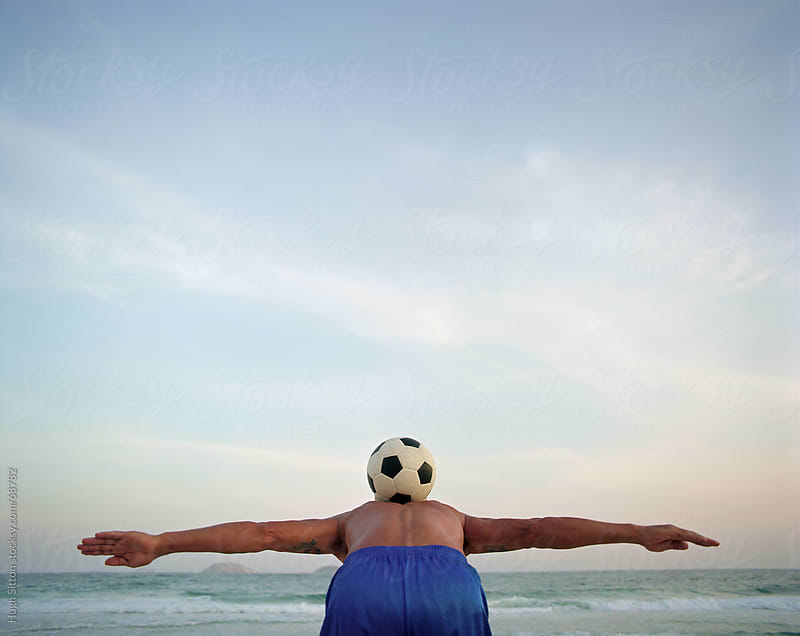 Man balancing soccer ball on his back. Rio. Brazil by Hugh Sitton for Stocksy United