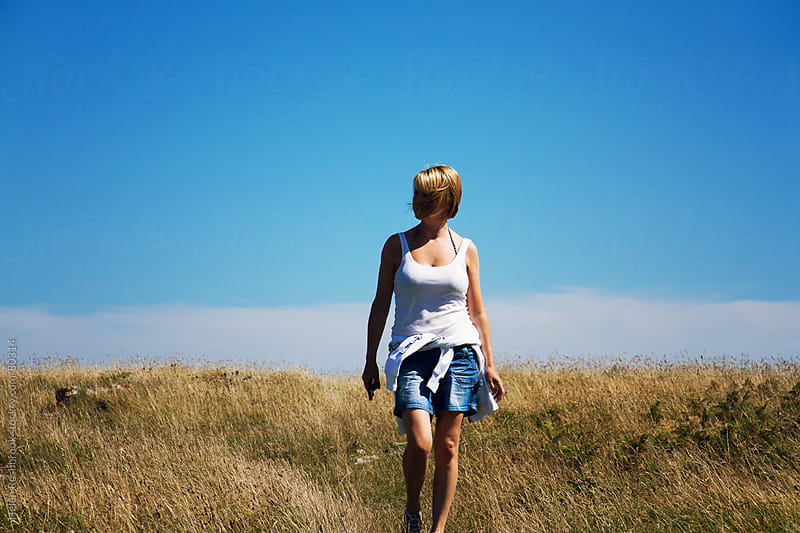A woman walking across heath land on a summer's day. by Helen Rushbrook for Stocksy United