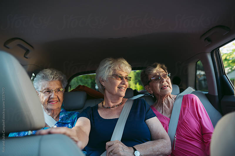 Happy, caucasian seniors having fun in back seat of car by Rob and Julia Campbell for Stocksy United