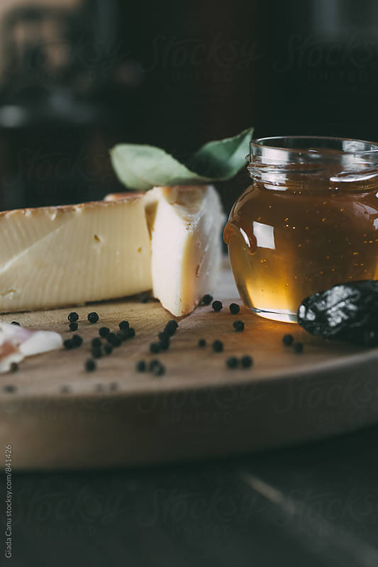 Cutting board with taleggio cheese, honey and pancetta by Giada Canu for Stocksy United