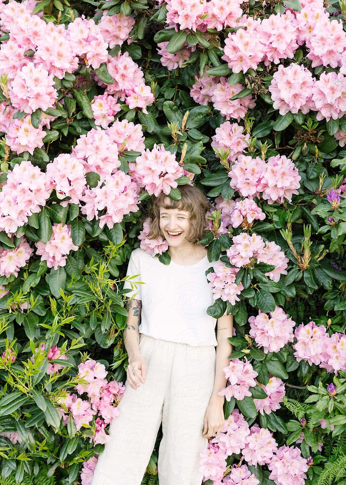 Portrait Of Girl Laughing In Pink Flower Bush Stocksy United