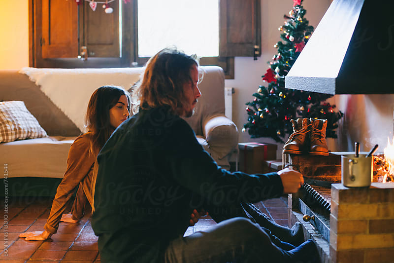Young couple resting by the fireplace at home. by BONNINSTUDIO for Stocksy United
