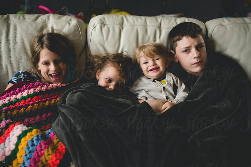 kids relaxing on the couch by Courtney Rust for Stocksy United