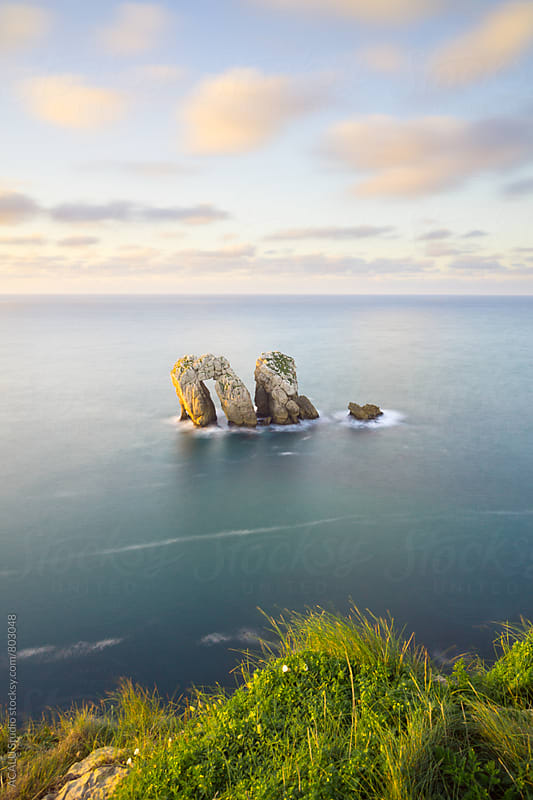 Stone arch in the sea from a cliff by ACALU Studio for Stocksy United