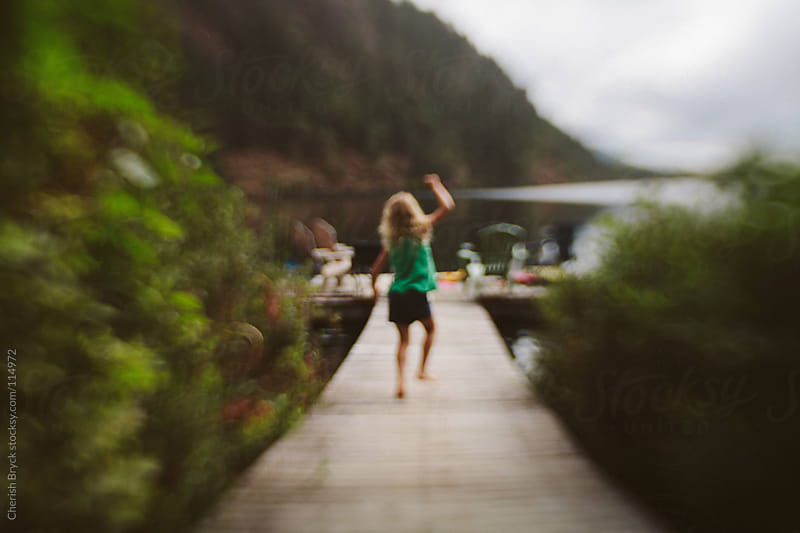 A young girl leaps for joy on a dock near a lake. by Cherish Bryck for Stocksy United