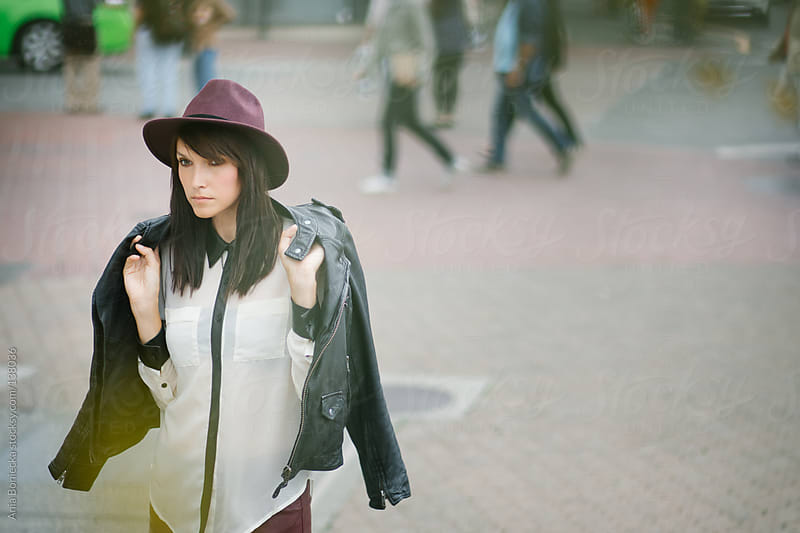 A stylish young brunette walking on the street by Ania Boniecka for Stocksy United