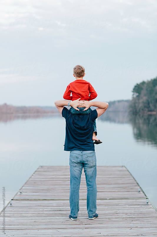 father and son standing on a pier by Kelly Knox for Stocksy United
