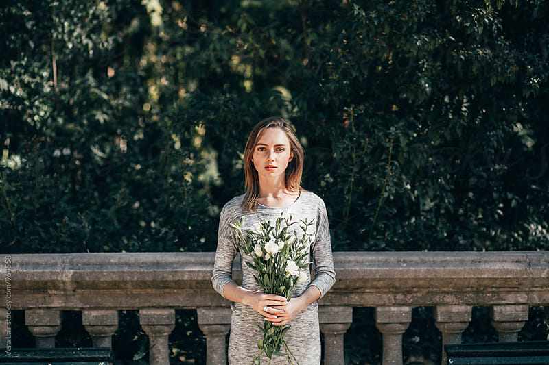 Young woman with a bouquet of white flowers by Vera Lair for Stocksy United