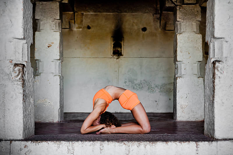 Woman doing yoga in a temple by Christine Hewitt for Stocksy United