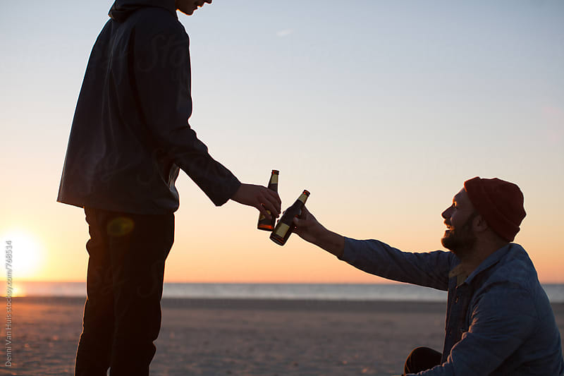 Celebrate. Two men drinking on the beach  by Denni Van Huis for Stocksy United