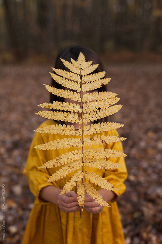 Girl hiding face behind a golden fern in autumn by Amanda Worrall for Stocksy United